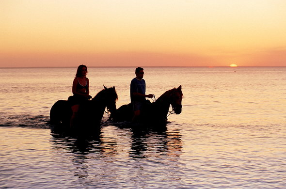 Romantic sunset horseride on the beach on Bazaruto Island.