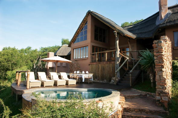 Impodimo Game Lodge pool deck with sun loungers.