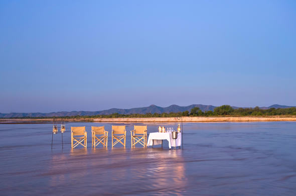 Relax while dining with your feet in the Kapamba River.