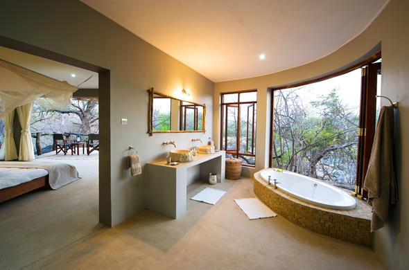 Luxury en-suite bathroom at Mkulumadzi with scenic views from the tub.