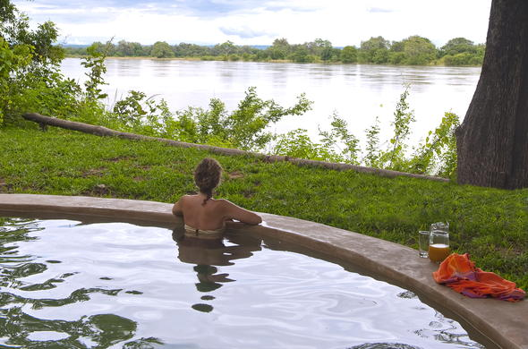 Guest enjoying picturesque river views from the pool.