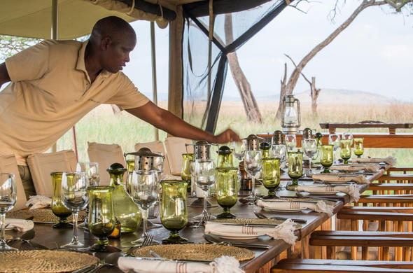 Staff member of Serengeti Safari Camp decorating the table for dinner.