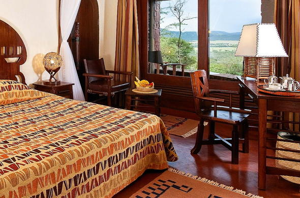 Cosy bedroom with scenic windows at Serengeti Serena Safari Lodge.