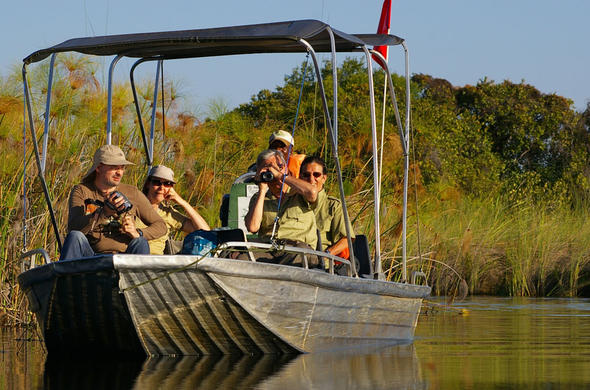 Guests take photographs on a boating safari.